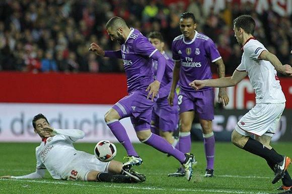 El jugador del Real Madrid, Benzema, regatea a varios jugadores sevillistas en la jugada que supuso el tercer gol y empate de su equipo ante el Sevilla FC. Foto: Paco Puentes/ El País.