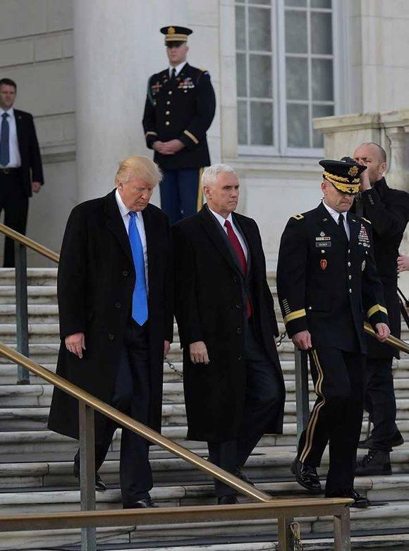 El presidente electo Donald Trump baja las escaleras del cementerio militar de Arlington junto a su vice Mike Pence y uno alto jefe castrense. Foto: AFP.