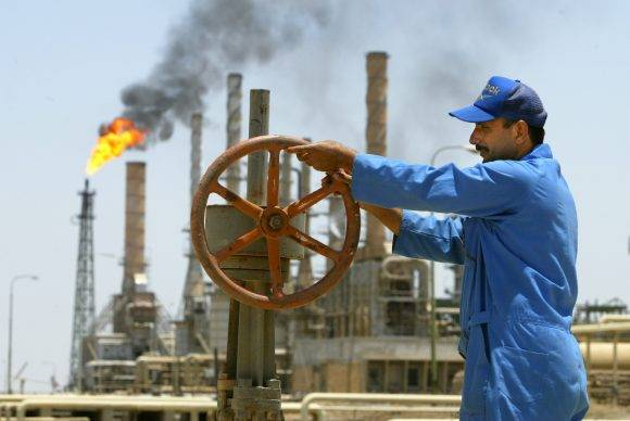 An Iraqi worker opens an oil pipeline at al-Shouayba refinery station in Basra June11, 2003. OPEC on Wednesday agreed to hold the line on oil output and called another meeting in seven weeks time in case recovering Iraqi exports undermine high prices. REUTERS/ Jamal Said IRAQ OIL