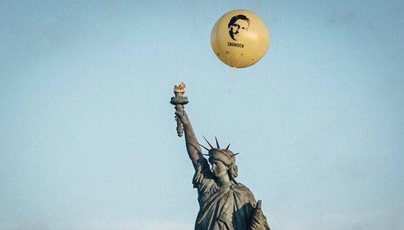 Integrantes de Amnistía Internacional colocaron ayer un globo con la imagen del ex contratista estadunidense Edward Snowden en la estatua de la Libertad, en demanda de que el mandatario otorgue un perdón presidencial al experto en informática, quien divulgó acciones de Washington sobre espionaje global. Foto tomada de Radio Universal.