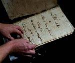 Un profesor de historia, el estadounidense David Lafevor, sostiene un registro de la era colonial en la iglesia del Espíritu Santo, en La Habana Vieja. Foto: AP.