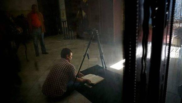 David Lafevor toma fotografías de registro de la época colonial en el interior de la iglesia de Espíritu Santo en La Habana Vieja. Foto: AP.