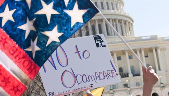 Un manifestante estadounidense porta una bandera nacional junto a una pancarta en contra de Obamacare delante del Capitolio en Washington D.C. Foto: Hispantv.