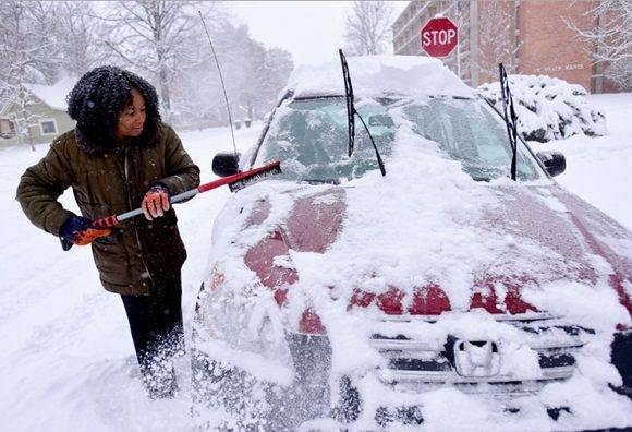 Una residente de Longmont, Colorado, despeja la nieve de su automóvil luego de una tormenta invernal. Foto Ap