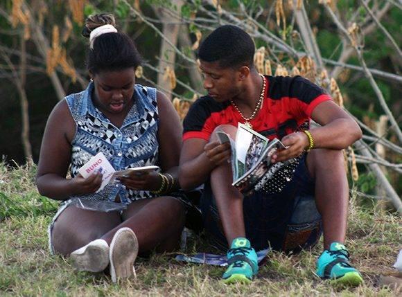 Una pareja lee libros recién comprados en las afueras de la Fortaleza San Carlos de la Canaña. Foto: Arlet Castillo/ Cubadebate.