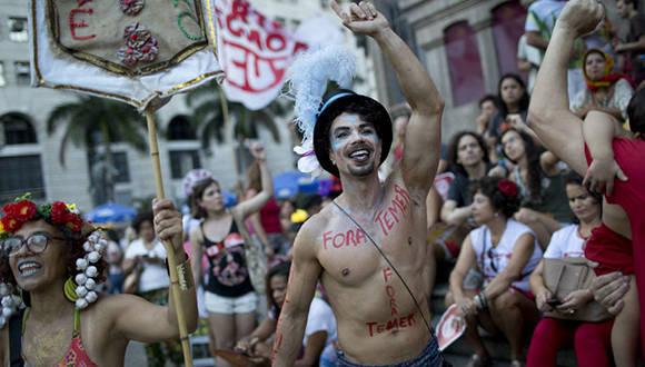 La política se hizo presente en el Carnaval de Río de Janeiro, donde los juerguistas llevan pancartas y pintadas como Fora Temer en alusión al presidente Michel Temer. Foto: Silvia Izquierdo/ AP.