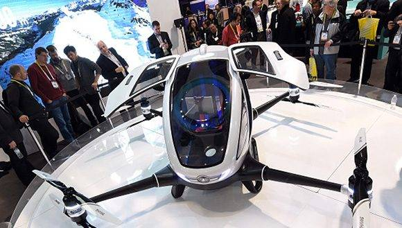 LAS VEGAS, NV - JANUARY 07:  Attendees look at an EHang 184 autonomous-flight drone that can fly a person at CES 2016 at the Las Vegas Convention Center on January 7, 2016 in Las Vegas, Nevada. The 18-foot-long, 440-pound drone has four arms and eight propellers and can fly up to 63 mph for 23 minutes and go about 20 miles. It can carry one passenger who does not need to pilot the drone. Once a destination is entered, only a take off or land button needs to be pushed to travel. The drone takes off and lands vertically eliminating the need for a runway. CES, the world's largest annual consumer technology trade show, runs through January 9 and features 3,600 exhibitors showing off their latest products and services to more than 150,000 attendees.  (Photo by Ethan Miller/Getty Images)