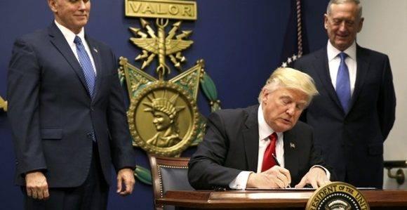 El presidente Donald Trump firma la orden que establece un control extremo de las personas que llegan a Estados Unidos después de asistir al juramento del secretario de Defensa, James Mattis (R), con el vicepresidente Mike Pence en Washington. REUTERS / Carlos Barria