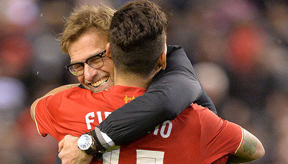 Liverpool's German manager Jurgen Klopp (L) embraces Liverpool's Brazilian midfielder Roberto Firmino after winning the penalty shoot-out in the English League Cup semi-final second leg football match between Liverpool and Stoke City at Anfield in Liverpool, north west England, on January 26, 2016. Liverpool won the two legged semi-final 6-5 on penalties, after a 1-0 Stoke victory in 90 minutes meant the tie finished 1-1 after extra time. / AFP / Paul ELLIS / RESTRICTED TO EDITORIAL USE. No use with unauthorized audio, video, data, fixture lists, club/league logos or 'live' services. Online in-match use limited to 75 images, no video emulation. No use in betting, games or single club/league/player publications.  /         (Photo credit should read PAUL ELLIS/AFP/Getty Images)