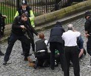 Un policía apunta un arma hacia un hombre tirado en el piso en la zona de acceso al Parlamento de Westminster.Derechos de autor de la imagen. Foto: PA.