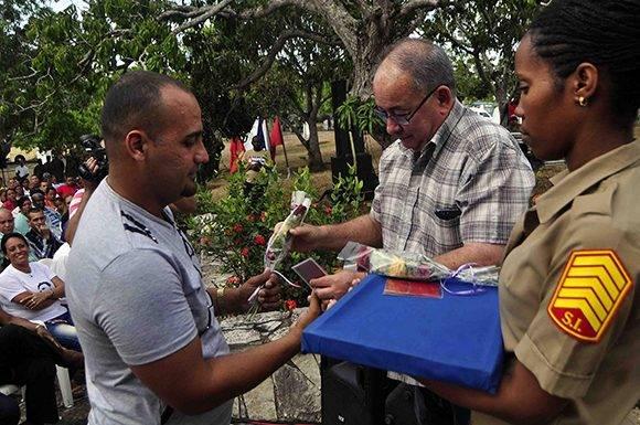 Lázaro Expósito Canto (C),  Primer Secretario del Comité Provincial del Partido Comunista de Cuba (PCC), entrega a un trabajador, el carné de militante del PCC, en el acto por el 139 Aniversario de la Protesta de Baraguá, en el Consejo Popular Baraguá del municipio Mella, en la provincia de Santiago de Cuba, el 15 de marzo de 2017.      Foto: ACN/  Miguel Rubiera.