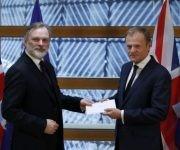 El representante de Reino Unido ante la Unión Europea, Tim Barrow, hace entrega al presidente de la Comisión Europea, Donald Tusk, de la carta formalizando la intención del país de salirse del bloque económico. Foto: Reuters.