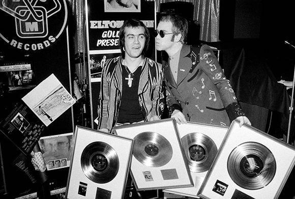 Elton John, a la derecha, con el compositor Bernie Taupin, durante una ceremonia en 1973 en la que se les premió con cuatro discos de oro por los álbumes que habían creado juntos. Foto: Michael Putland/ Getty Images.
