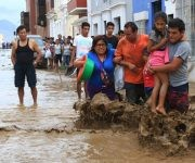 Local residents wade through the water as a flash flood hits the city of Trujillo, 570 kilometres north of Lima on March 18, 2017, bringing mud and debris. The El Nino climate phenomenon is causing muddy rivers to overflow along the entire Peruvian coast, isolating communities and neighbourhoods. Thousands have been affected since January, and 72 people have died. Most cities face water shortages as water lines have been compromised by mud and debris. / AFP PHOTO / CELSO ROLDAN AND STR