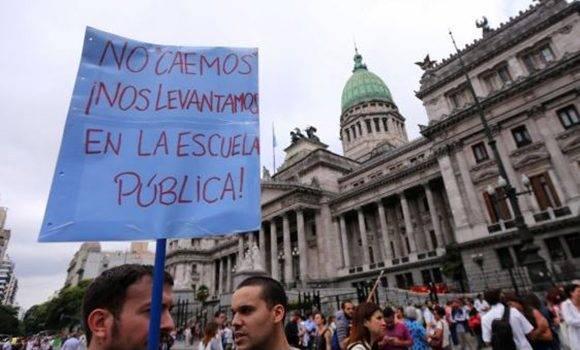 """Un manifestante sostiene un letrero que dice: """"No caemos en la escuela pública"""" frente al Congreso después de la gafe de ayer del presidente argentino Mauricio Macri sobre los argentinos que """"caen en la escuela pública"""" durante una protesta en Buenos Aires Aires. Foto: REUTERS / Marcos Brindicci"""