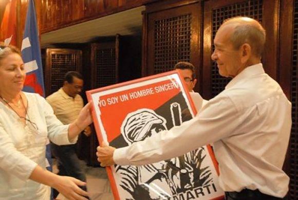 El periodista Eduardo Yasells, Premio Nacional de Periodismo José Martí por la obra de la vida, recibe una felicitación especial durante el acto por el Día de la Prensa cubana. Foto: Yoandry Avila Guerra/ Cubaperiodistas.