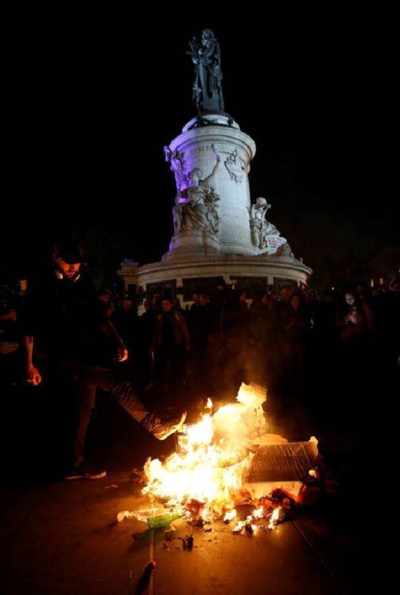 Manifestante quema cartel con la imagen de Marine Le Pen. Foto: Reuters.