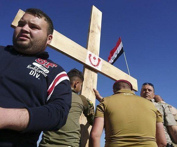 Un grupo de vecinos de un barrio musulmán de Mosul levanta hoy una cruz al lado de un monasterio para alentar a los cristianos a volver a la ciudad iraquí, en cuya zona oeste prosigue la ofensiva contra el grupo terrorista Estado Islámico. Foto: EFE.