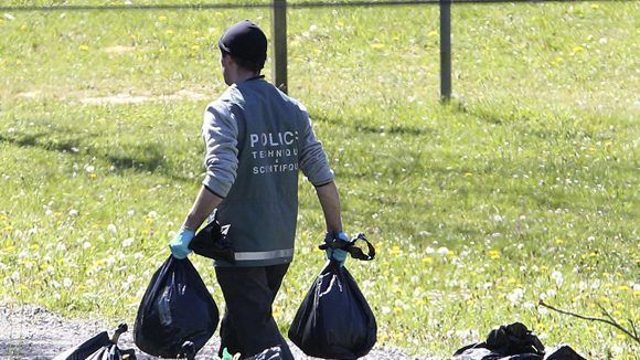 Un policía francés lleva dos bolsas de plástico con armamento de ETA. Foto: AP.