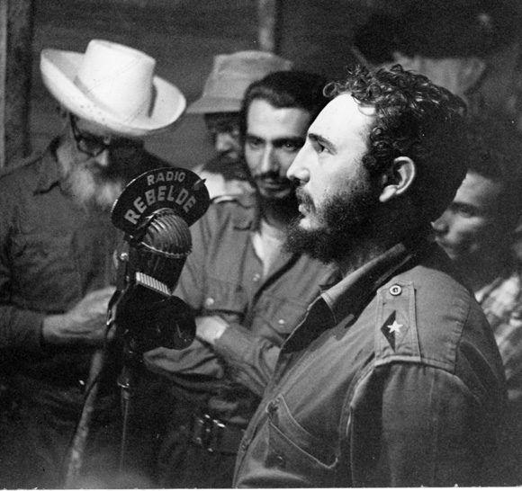 En el mismo local desde donde la emisora Radio Rebelde trasmitía en los últimos meses de la guerra de liberación, Fidel comunica al pueblo el trascendental acontecimiento. Al centro el Capitán Jorge Enrique Mendoza, quien fuera uno de sus locutores y el Comandante Crescencio Pérez.