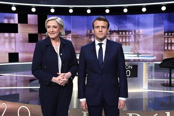 Los dos candidatos presidenciales franceses: Le Pen y Macron, antes de comenzar el debate televisado. Foto: AFP.