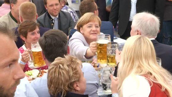 La canciller alemana Angela Merkel alza su tarro de cerveza durante una campaña electoral de su Unión Demócrata Cristiana y la Unión Social Cristiana, en Munich. Foto: AP.