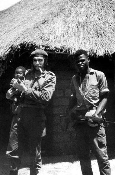 El Che sostiene en brazos a un bebé junto a un combatiente congoleño.