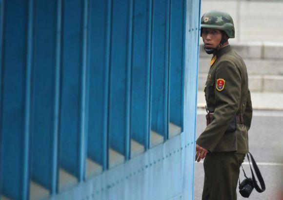 Un soldado norcoreano mira a la localidad de Panmunjom, en su vecina del Sur, en la Zona Desmilitarizada. Foto: AFP.