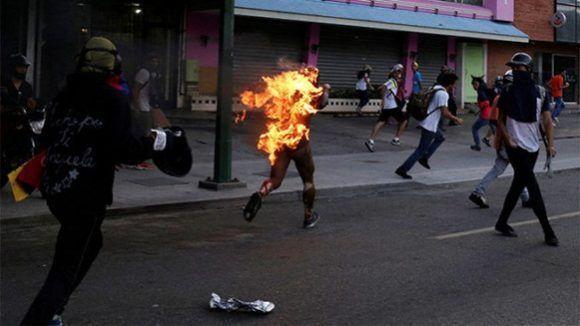 Un hombre al que prendieron fuego camina envuelto en llamas por Caracas, Venezuela, durante las protestas de la oposición contra el presidente del país, Nicolas Maduro, el 20 de mayo de 2017. Marco Bello / Reuters