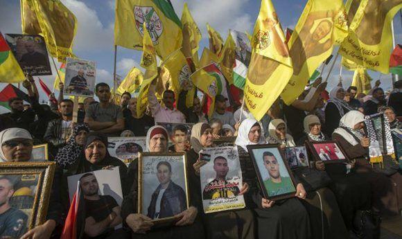 Manifestantes alzan las fotografías de sus familiares palestinos presos en Israel. Foto: EFE.