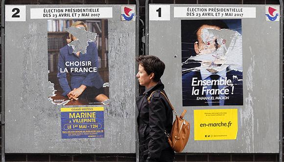 Una mujer camina cerca de carteles desgastados con el mensaje de Marine Le Pen (izq.) y Emmanuel Macron. Foto:  Getty Images.