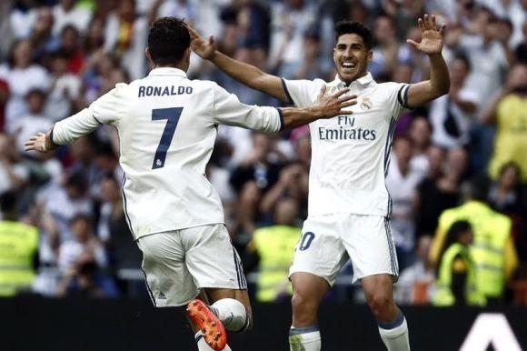 El delantero portugués del Real Madrid Cristiano Ronaldo (i) celebra con su compañero Marcos Asensio (d), el gol que ha marcado, el segundo del equipo frente al Sevilla, durante el encuentro correspondiente a la jornada 37 de primera división, que disputaron en el estadio Santiago Bernabéu, en Madrid. Foto: EFE.