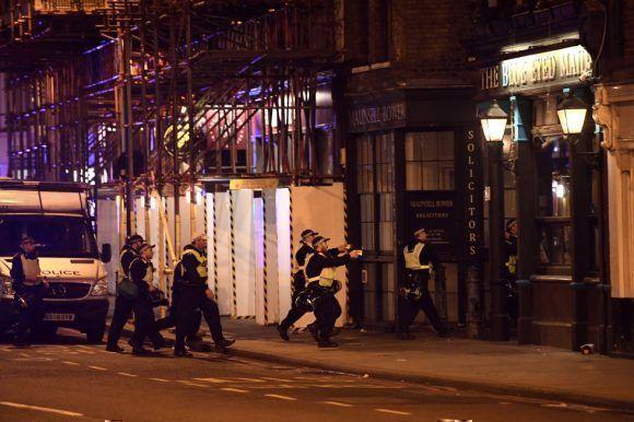Un grupo de policías armados inspecciona un edificio cerca del puente de Londres. Foto: Getty Images.