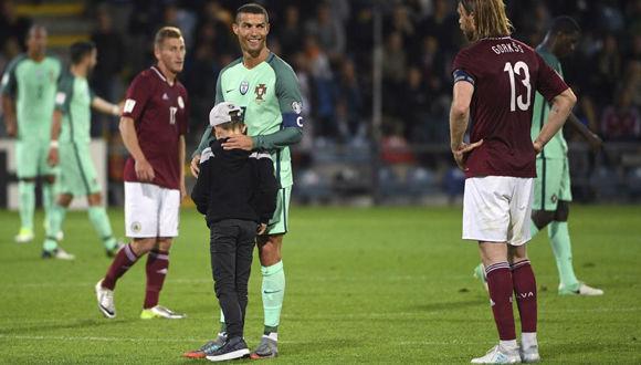 Un niño saltó al campo en pleno partido Portugal-Letonia y Cristiano Ronaldo  fue a abrazarle y hasta bromeó con él, antes de  que las fuerzas de seguridad lo sacaran del terreno. Foto: AP.