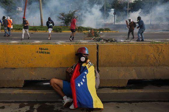 Un manifestante de la derecha venezolana se esconde mientras sus compañeros lanzan explosivos. Foto: EFE.