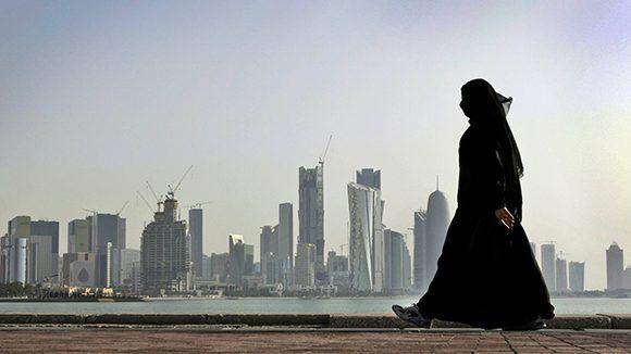 Una mujer camina frente a los rascacielos de Doha, Qatar. Foto: AP.