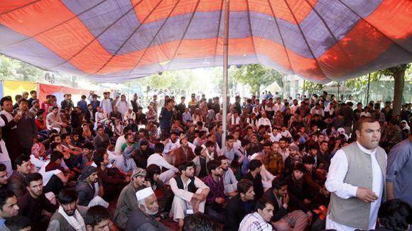 Un grupo de manifestantes afganos se sientan en un campamento cerca del palacio presidencial afgano mientras exigen la renuncia de funcionarios de seguridad en Kabul. Foto: EFE.