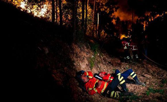 Los bomberos toman un descanso mientras el fuego continúa ardiendo detrás. Foto: AFP.