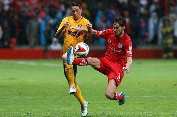 Fernando Torres y Santiago García disputan por el balón durante el empate sin goles entre el Atlético de Madrid y el Toluca. Foto: Reuters.