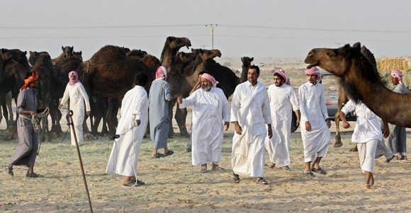 Un grupo de personas con sus camellos, en la zona del desierto de Arabia Saudí que linda con Qatar. Foto: Reuters.