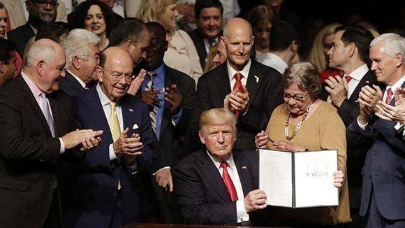Donald Trump firma la orden ejecutiva que da marcha atrás a algunas de las medidas que impulsaron las relaciones Cuba- Estados Unidos. Foto: AP.