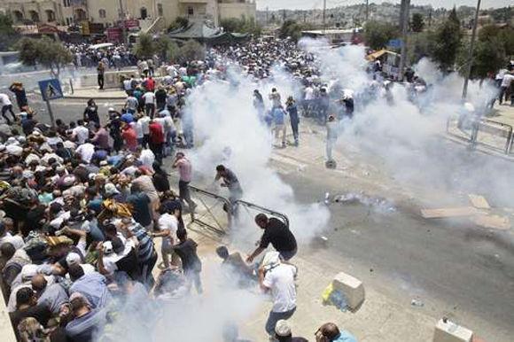 Palestinos escapan del gas lacrimógeno lanzado por policías israelíes fuera de la ciudad vieja de Jerusalén. Israel ha restringido el acceso musulmán a la Explanada de las Mezquitas e instaló detectores de metal en el sitio santo. Foto: AP.