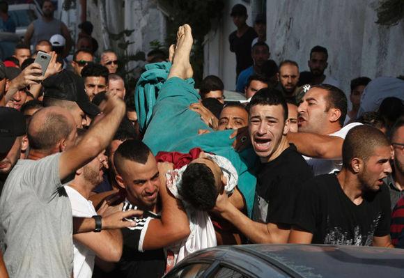 Varios hombres llevan el cuerpo de un hombre muerto por un disparo durante los disturbios en Jerusalén Este. Foto: AFP.