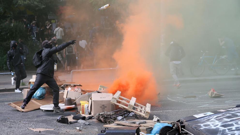 Un manifestante lanza una botella a la policía en los disturbios de este viernes en Hamburgo. Foto: AFP.