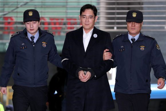 Jay Y. Lee, co-vice chairman of Samsung Electronics Co., center, is escorted by police officers as he arrives at the special prosecutors' office in Seoul, South Korea, on Sunday, Feb. 19, 2017. Lee was taken back to a special prosecutor's office for a second day following a second night in police custody as part of a corruption probe that has widened to include South Korea's largest industrial conglomerate. Photographer: SeongJoon Cho/Bloomberg via Getty Images