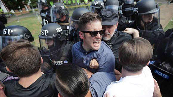 Los supremacistas blancos dicen apoyar a Donald Trumo y se sienten identificados con el presidente de Estados Unidos. En la imagen. El supremacista blanco Richard Spencer, el sábado al ser desalojado por la policía en la protesta de Charlottesville. Foto: AFP.
