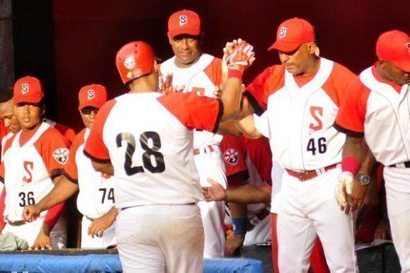 Lionard Kindelán (28), es recibido por su padre y director del equipo de Santiago de Cuba, Orestes Kindelán (46), luego de conectar un cuadrangular, que empató el juego a una carrera, en el sexto ining, donde los santiagueros ganaron 3 carreras por 2, en partido celebrado en el estadio Guillermón Moncada de Santiago de Cuba. Foto: Miguel Rubiera/ ACN.