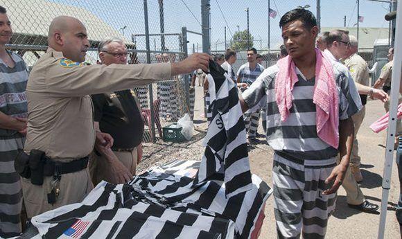 Los presos reciben un nuevo uniforme con la bandera de EEUU en un acto ante la prensa en la cárcel en julio de 2016. Foto: Gary Williams/ EFE.