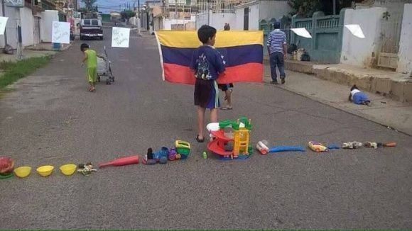 Niño jugando a trancar una calle. Foto: Twitter