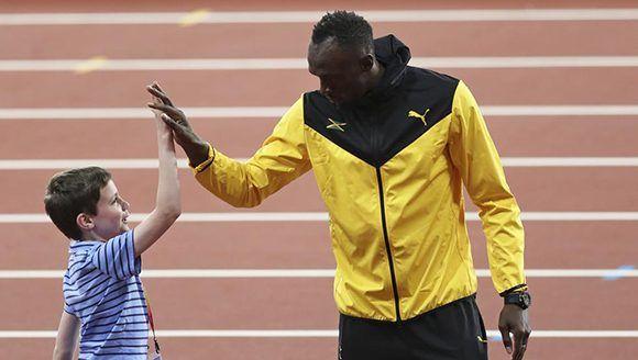 Bolt saluda a un pequeño admirador en la última jornada de Londres-2017. Foto: AP.